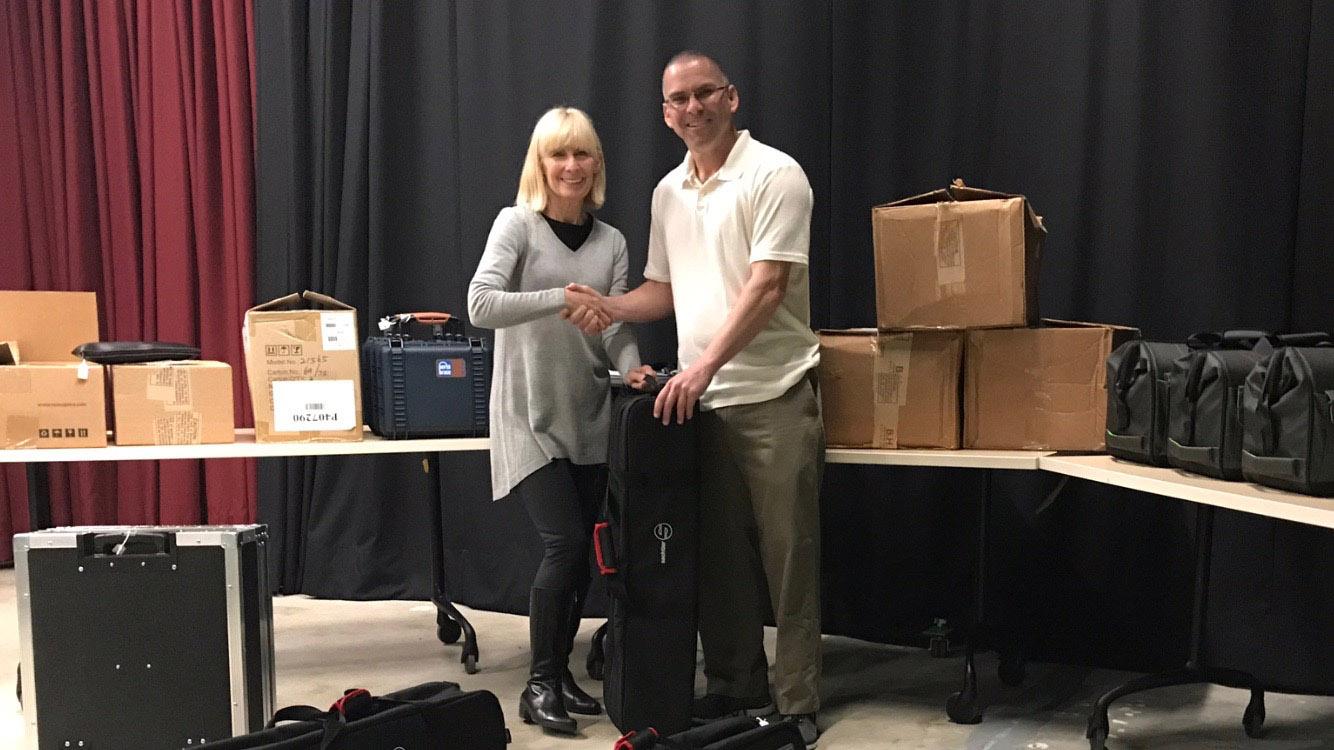 Joel Domhoff, of Aptos High School, receives mobile studio equipment from TV.